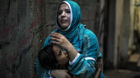 A Palestinian woman hugs her daughter at the site of an explosion in a public playground in the beachfront Shati refugee camp in Gaza City on July 28, 2014. Palestinian medical sources blamed death of at least seven Palestinian children on air strikes launched by the Israeli military, which in turn said Hamas had misfired its own rockets at the camp and at the Shifa hospital.