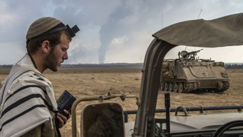 An Israeli soldier prays on the Israeli side of the border with Gaza on July 29 as smoke billows from the only power plant supplying electricity to Gaza.