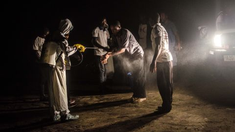 Red Cross volunteers disinfect each other with chlorine after removing the body of an Ebola victim from a house in Pendembu on July 18, 2014.