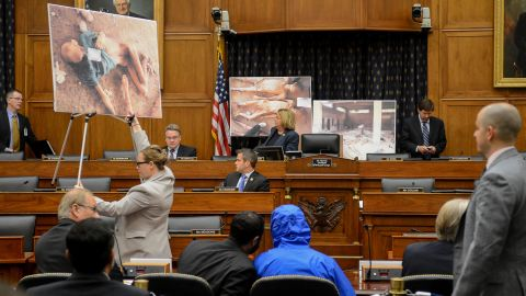 """Photographs of victims of the Bashar al-Assad regime are displayed as a Syrian Army defector known as """"Caesar,"""" center, appears in disguise to speak before the House Foreign Affairs Committee in Washington. The briefing on Thursday, July 31, was called """"Assad's Killing Machine Exposed: Implications for U.S. Policy."""" Caesar was apparently a witness to al-Assad's brutality and has <a href=""""http://www.cnn.com/2014/08/04/world/meast/syria-crisis-remember/index.html"""">smuggled more than 50,000 photographs</a> depicting the torture and execution of more than 10,000 dissidents."""