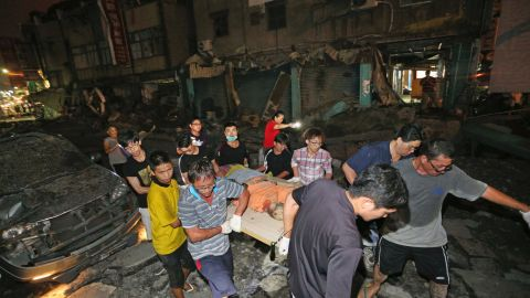 The body of a victim killed in the explosions is carried from the scene.