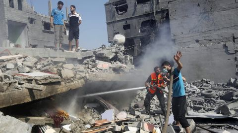 Palestinians extinguish a fire in the wreckage of a building, which was hit in an Israeli strike, in Rafah, in the southern Gaza Strip on August 2, 2014.