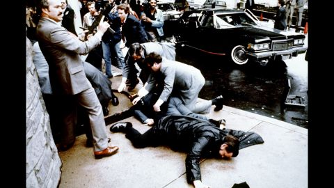 """Police and Secret Service agents react during <a href=""""http://www.cnn.com/2013/07/17/us/gallery/crimes-of-the-century-reagan/index.html"""">the Reagan assassination attempt,</a> which took place March 30, 1981, after a conference outside the Hilton Hotel in Washington. Lying on the ground in front is wounded police officer Thomas Delahanty. Brady is behind him, also lying face down."""