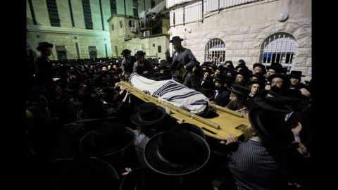 """The body of Avrohom Wallis is carried during his funeral in Jerusalem on Monday, August 4. Wallis was killed in what Israeli police spokesman Micky Rosenfeld called a """"terror attack,"""" when a man drove an earthmover into a bus in Jerusalem."""