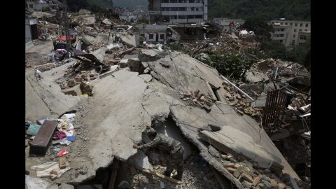 A military rescue worker searches for missing people amid the rubble of destroyed houses in Longtoushan, a township in southwest China's Yunnan province, on Wednesday, August 6.