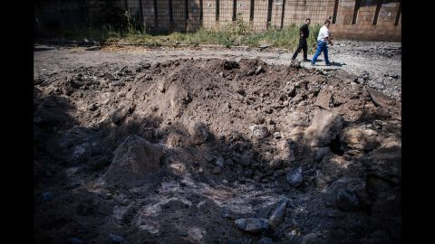 Men walk past a bomb crater in Donetsk on August 6.