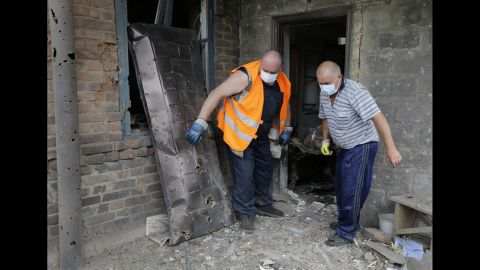 Rescue workers carry the body of a woman who was killed during a bomb shelling in Donetsk on August 5.