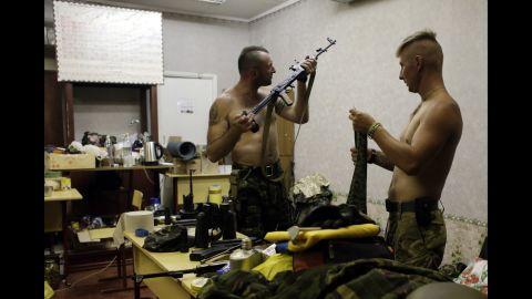 Ukrainian servicemen from the Donbass volunteer battalion clean their guns Sunday, August 3, in Popasna, Ukraine.