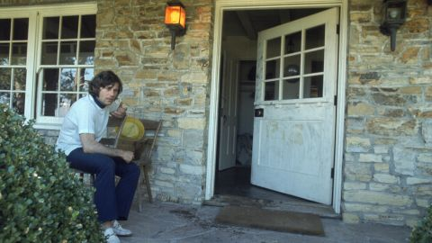"""Polanski, who was out of town at the time of the murders, is seen on the porch outside his home. The remnants of the word """"pig"""" can be seen where it was scrawled on the door."""