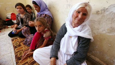 An Iraqi Yazidi family that fled the violence in the northern Iraqi town of Sinjar, sit at at a school where they are taking shelter in the Kurdish city of Dohuk in Iraq's autonomous Kurdistan region, on August 5, 2014. Islamic State (IS) Sunni jihadists ousted the Peshmerga troops of Iraq's Kurdish government from the northern Iraqi town of Sinjar, forcing thousands of people from their homes. The Yazidis, are a small community that follows a 4,000-year-old faith and have been repeatedly targeted by jihadists who call them 'devil-worshipers' because of their unique beliefs and practices. AFP PHOTO/SAFIN HAMED (Photo credit should read SAFIN HAMED/AFP/Getty Images)