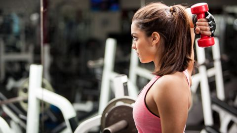 Gorgeous young woman using dumbbells to work on her triceps.