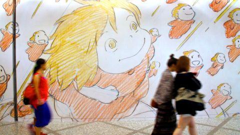 Visitors at a Studio Ghibli exhibit in Hong Kong walk by a wall of artwork.