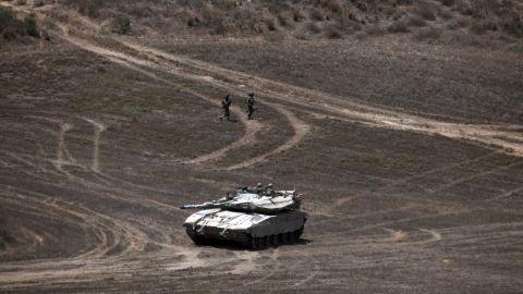 Israeli soldiers walk past a Merkava tank as they patrol a field near Israel's border with Gaza on August 9.