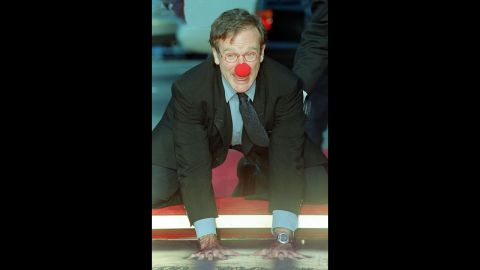 """Williams wears a clown nose as he places his hands in concrete during a ceremony outside Mann's Chinese Theatre in Hollywood in 1998. In the critically acclaimed """"Patch Adams,"""" he played a doctor who used humor to help heal his patients"""
