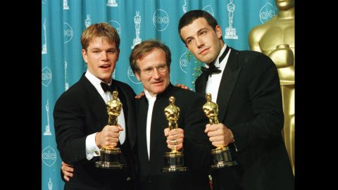 """Actor-writers Matt Damon, left, and Ben Affleck, right, pose with Williams, holding the Oscars they won for """"Good Will Hunting"""" at the 70th annual Academy Awards in 1998. Damon and Affleck won for best original screenplay, and Williams won for best supporting actor."""