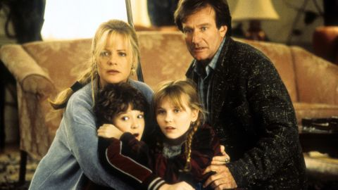 """From left, Bonnie Hunt, Bradley Pierce, Kirsten Dunst and Williams hold one another in a scene from the 1995 film """"Jumanji."""""""