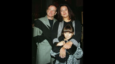 """Williams and his wife, Marsha, pose for photographers with their daughter, Zelda, as they arrive at the premiere of the film """"Patch Adams"""" in December 1998 in New York City."""