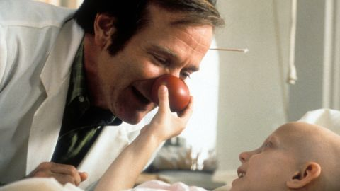 """Williams visits a sick child in a scene from the film """"Patch Adams"""" in 1998."""