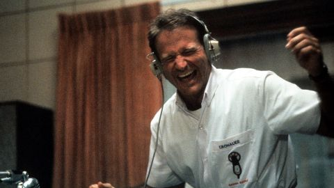 """Williams enjoys music through a headset in a scene from the film """"Good Morning, Vietnam"""" in 1987."""