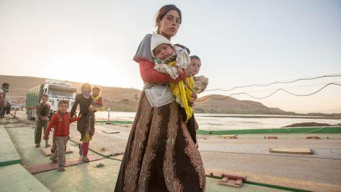 A Yazidi woman holding he baby crossing the bridge to Iraqi Kurdistan.