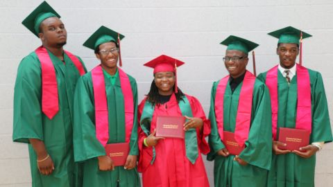 Michael Brown (far left), the teen shot and killed by Ferguson, Missouri police August 9, 2014, stands with fellow graduates at Normandy High School Summer graduation. The May class had 120 graduates, the summer class had 11 graduates. MUST CREDIT:  Normandy Schools Collaborative/Daphne J. Dorsey
