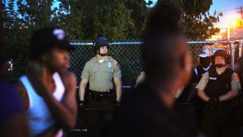 Police stand guard among demonstrators on August 13, 2014