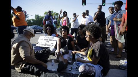 A small group of protesters block traffic in the street before police arrived on August 13, 2014.