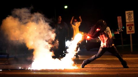 A protester throws a tear gas canister back toward police on August 13, 2014.