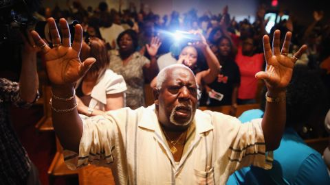People congregate at the Greater St. Marks Family Church in St. Louis along with the family of Michael Brown and the Rev. Al Sharpton on August 12, 2014.