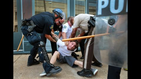 Police officers arrest a man who refused to leave when police cleared streets in Ferguson on August 11, 2014.