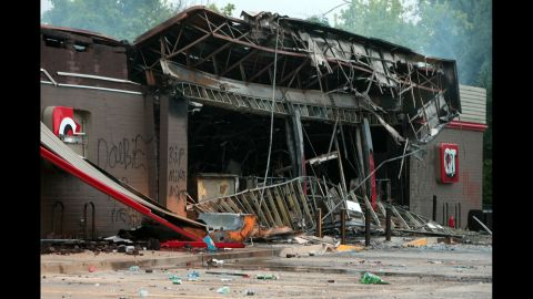 A burned-out QuikTrip gas station smolders on August 11, 2014 after protesters looted and burned the Ferguson building the night before.