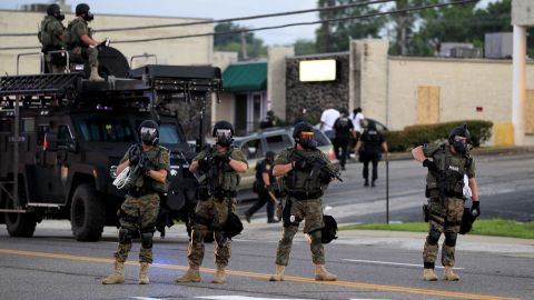 Police wearing riot gear try to disperse a crowd Monday, August 11.