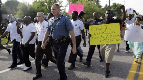 Thousands of demonstrators march down a Ferguson street with members of the St. Louis County Police and the Missouri State Highway Patrol on Thursday, August 14, 2014.