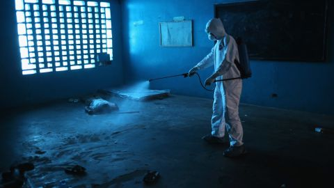 A health worker disinfects a corpse after a man died in a classroom being used as an Ebola isolation ward August 15, 2014, in Monrovia.