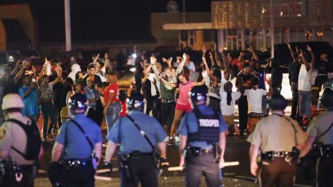 Missouri State Highway Patrol officers listen to taunts from demonstrators during a protest on Friday, August 15, 2014.