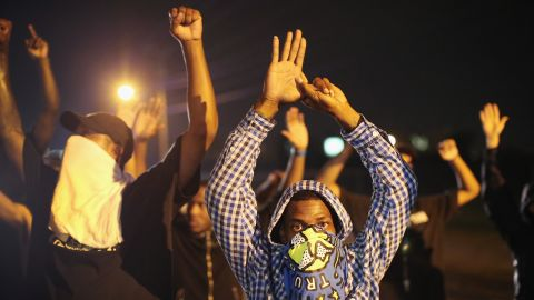 """Demonstrators protest with their hands up on August 15, 2014. The """"hands up"""" gesture has become a symbol in protests as Brown, according to eyewitnesses, was trying to surrender when he was shot multiple times."""