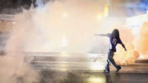 A demonstrator throws a tear gas canister back at police on August 15, 2014.