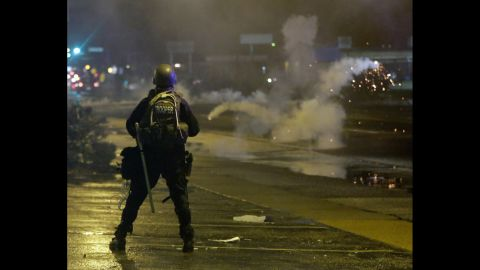 A law enforcement officer watches as tear gas is fired to disperse a crowd on August 17, 2014.