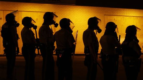 Police wait to advance after using tear gas to disperse protesters August 17, 2014.