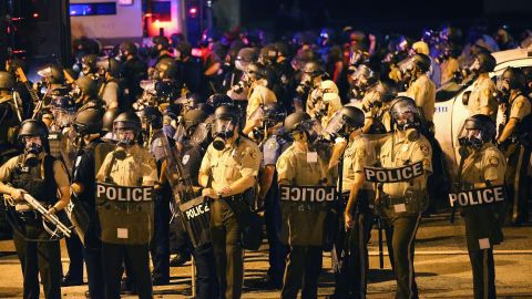 A large group of police officers advance toward protesters on August 17, 2014.