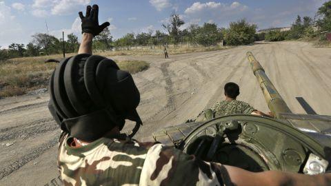 Pro-Russian rebels greet each other as they pass near Krasnodon, Ukraine, on August 16.
