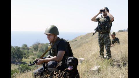 Ukrainian border guards patrol near Novoazovsk on Friday, August 15.