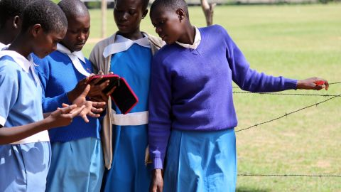 A group of female students gather around an e-reader in Amogoro. The devices can hold a charge for up to two weeks, which is helpful in areas where electricity is scarce.