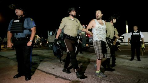 Police lead a man away during a protest August 18, 2014.