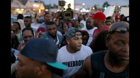 Musician Nelly, center, joins demonstrators in Ferguson on August 18, 2014.