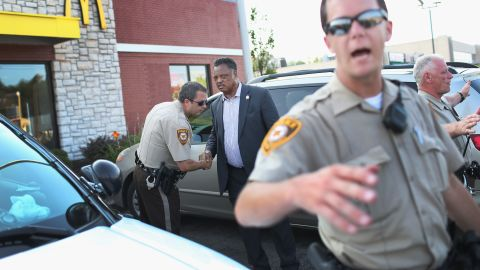 The Rev. Jesse Jackson shakes hands with a police officer as he visits Ferguson's demonstration area on August 18, 2014.