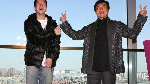"""Jackie Chan (right) poses with his son Jaycee in 2009 outside Beijing's """"Bird's Nest"""" olympic stadium."""