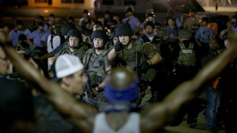 Police point out a demonstrator who has his arms raised before moving in to arrest him Tuesday, August 19, 2014.