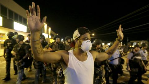 A man is moved by a line of police as authorities disperse a protest in Ferguson, Mo. early Wednesday, Aug. 20, 2014. On Saturday, Aug. 9, 2014, a white police officer fatally shot Michael Brown, an unarmed black teenager, in the St. Louis suburb. (AP Photo/Charlie Riedel/AP)
