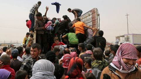 Displaced Iraqis receive clothes from a charity at a refugee camp near Feeshkhabour, Iraq, on Tuesday, August 19.